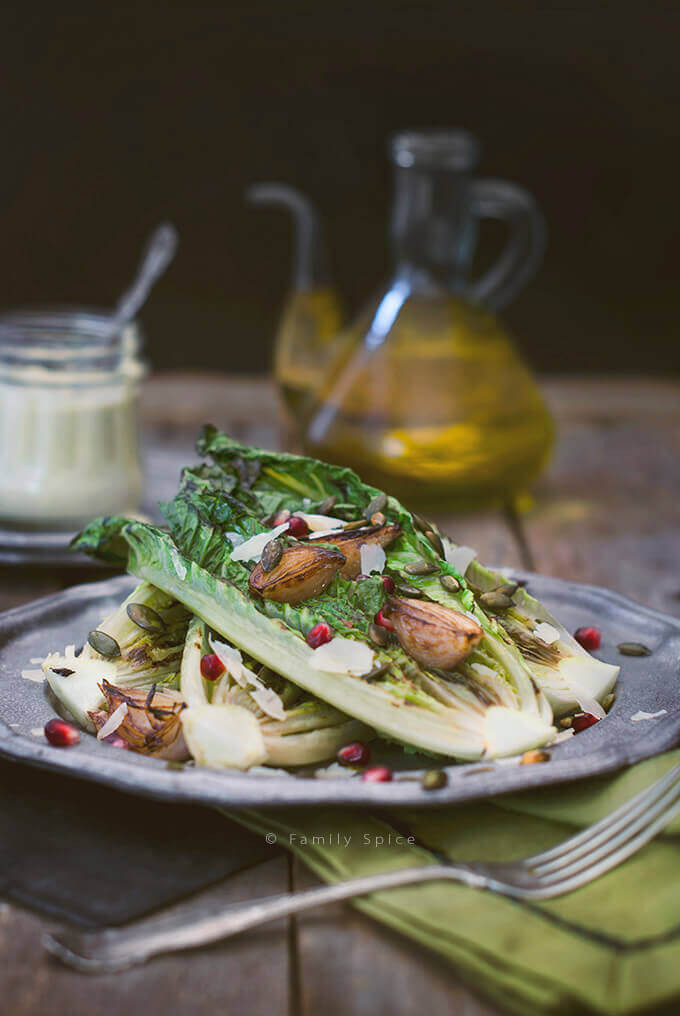 A dish with Grilled Caesar Salad with pomegranate, pepitas and shallots by FamilySpice.com
