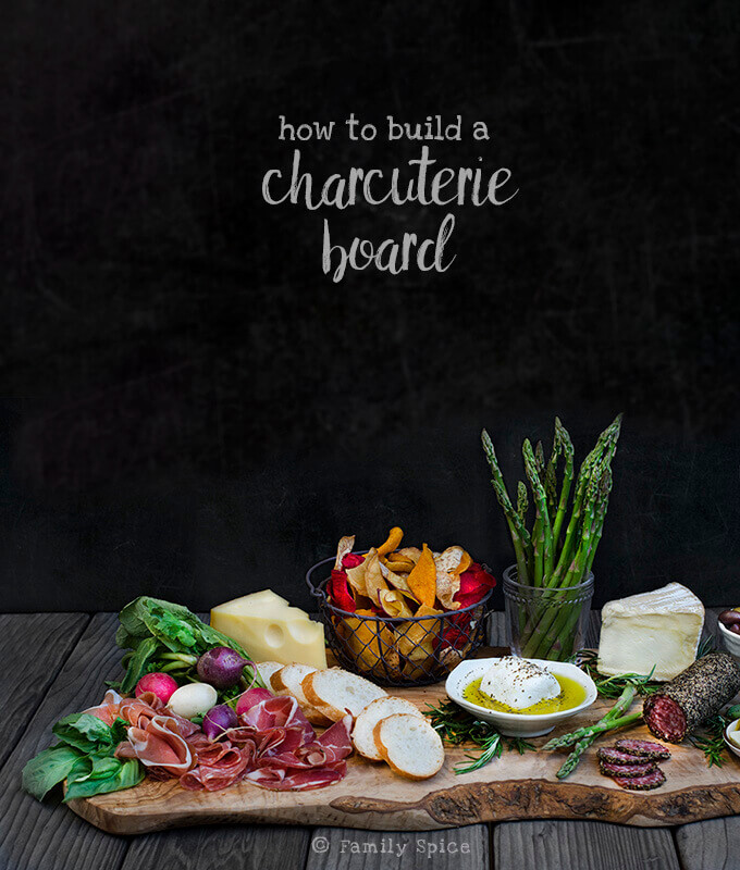 Side view of a charcuterie board that includes Italian meats, cheeses, slices of baguette, olives, herbs and vegetables