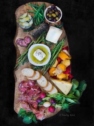 Charcuterie board that include Italian meats, feta, Swiss cheese, brie, root vegetable chips, olives, herbs and vegetables