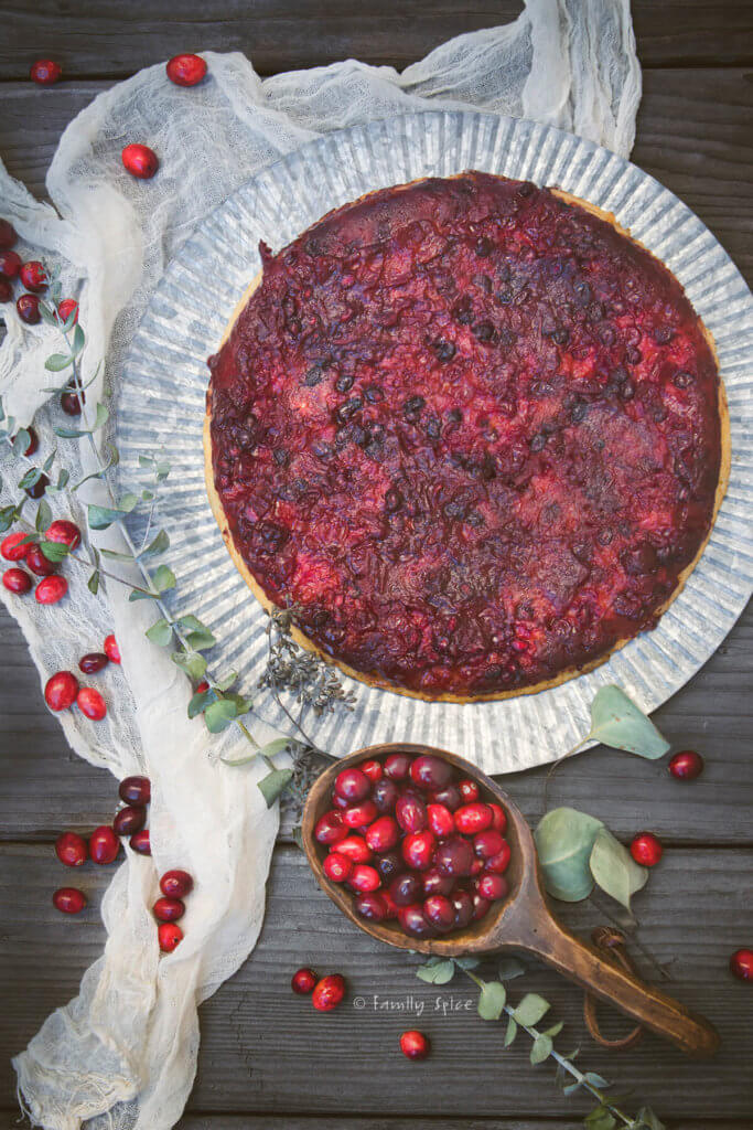 overhead view of cranberry upside down cake surrounded by fresh cranberries and eucalyptus branches