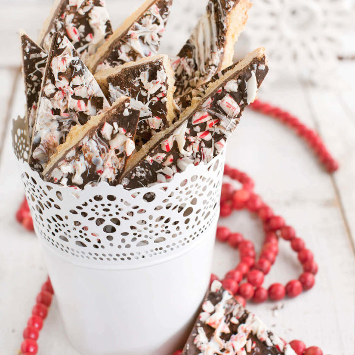 Several shortbread peppermint bark cookies in a white pail with a string of red beads around it