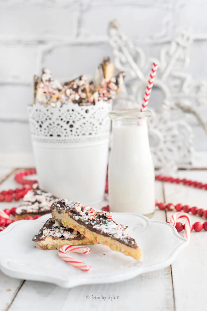 A couple of shortbread peppermint bark cookies on a white plate with a bottle of milk with a red and white straw