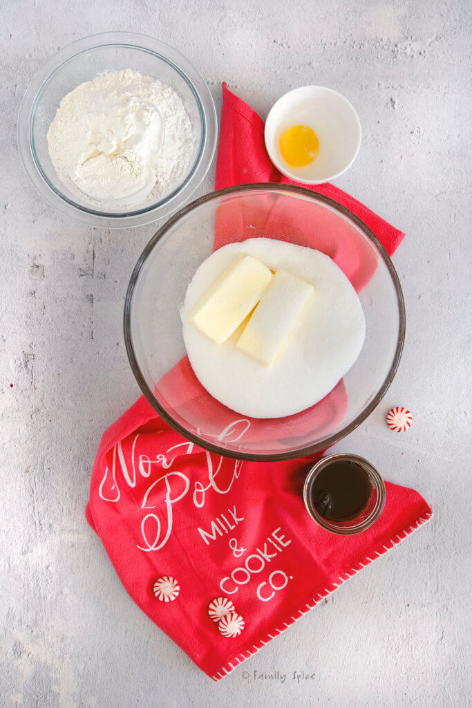 A bowl with butter and sugar with other cookie ingredients around it on a red kitchen towel