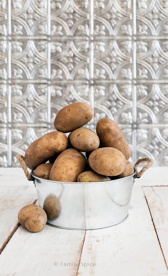 10-pounds of Idaho Potatoes in a metal bin by FamilySpice.com