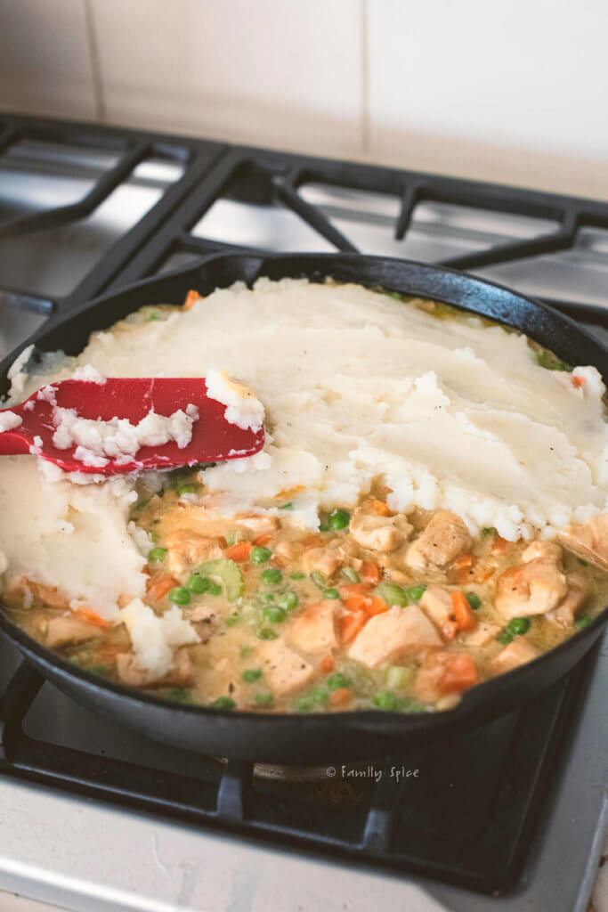 Adding mashed potato topping over chicken shepherds pie in a cast iron pan