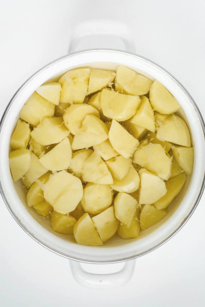 Chunks of potatoes in water in a white pot on a white background