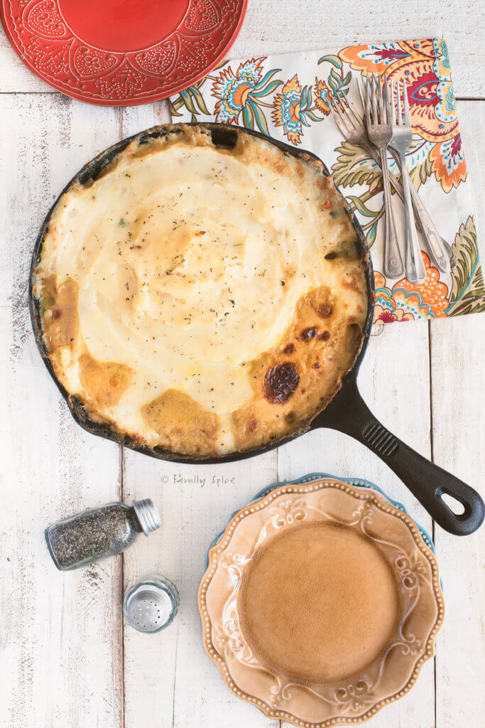 Top view of a cast iron skillet with Chicken shepherds pie with a floral napkin and a couple of plates