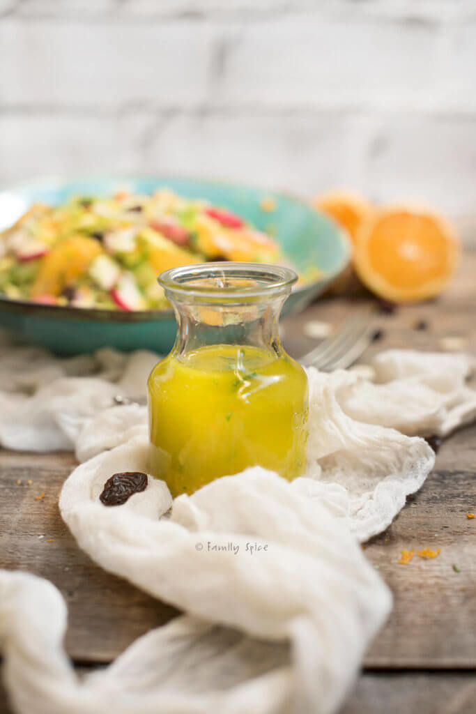 Closeup of a small bottle of vinaigrette with salad behind it