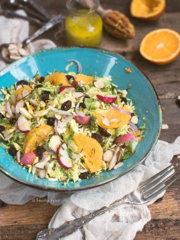 Closeup of a shaved brussels sprout salad with raisins and oranges
