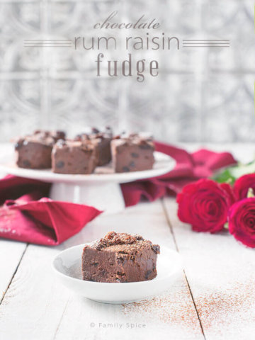 Closeup of Chocolate Rum Raisin Fudge on a White Cake Stand with Red Roses by FamilySpice.com