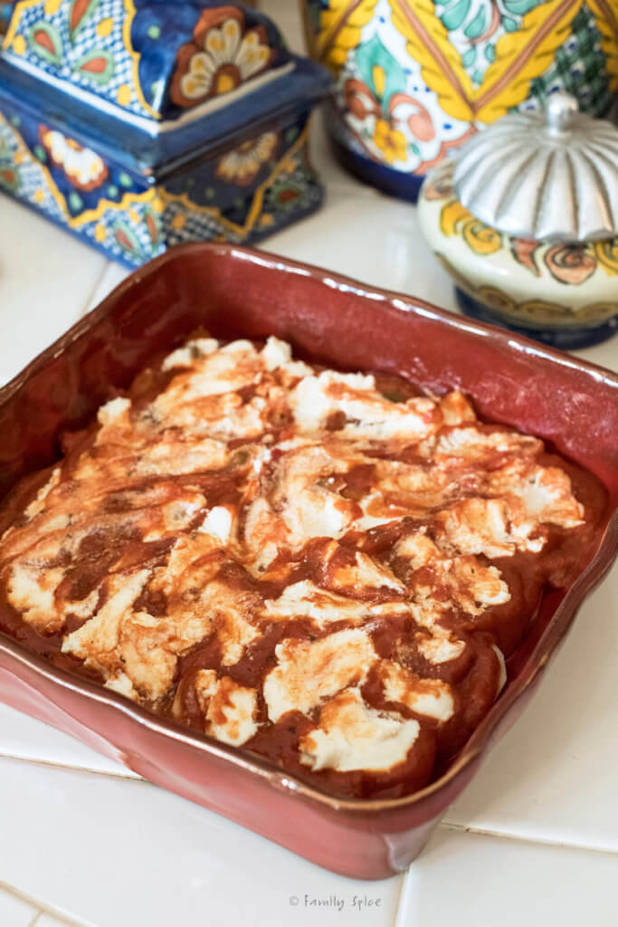 Ricotta cheese spread over marinara sauce in a red square baking dish