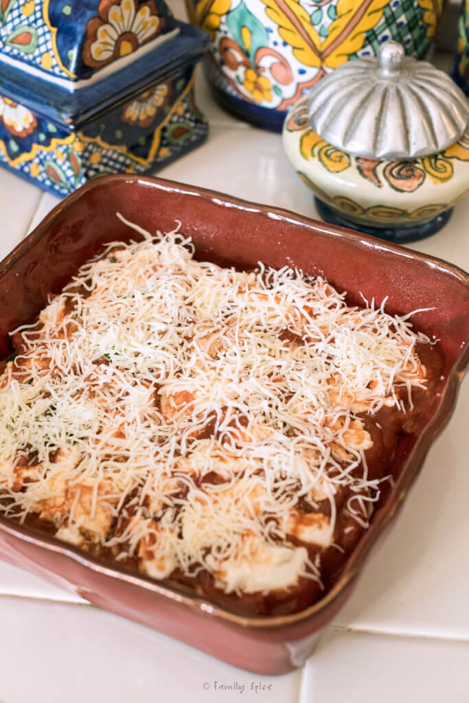Shredded and ricotta cheese spread over marinara sauce in a red square baking dish