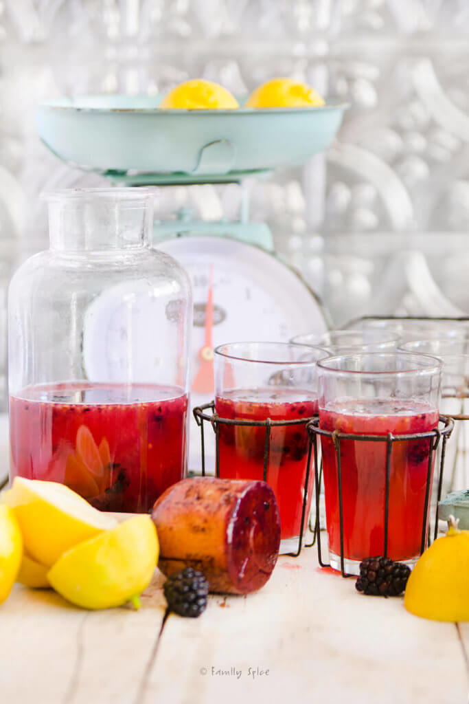 Side view of a bottle and glasses filled with blackberry lemonade with lemons, blackberries and an antique scale around it