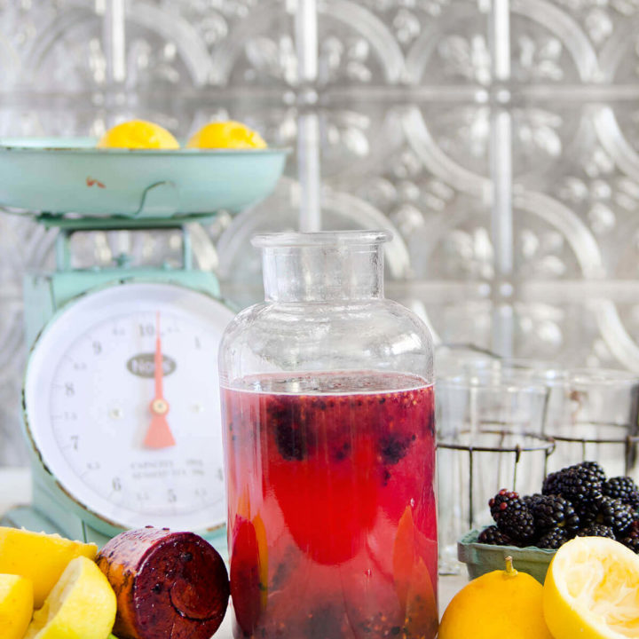 Side view of a bottle filled with blackberry lemonade with lemons, blackberries and an antique scale around it