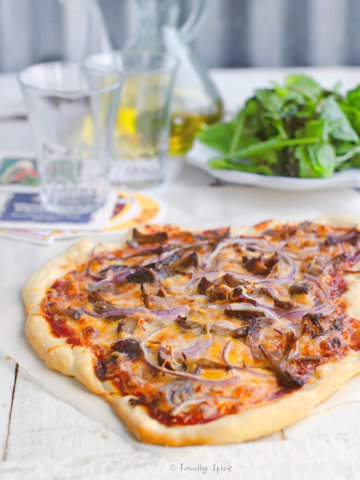 A rustic pulled pork pizza with olive oil and arugula behind it