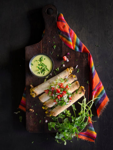 Several baked taquitos with steak on a dark cutting board with guacamole salsa