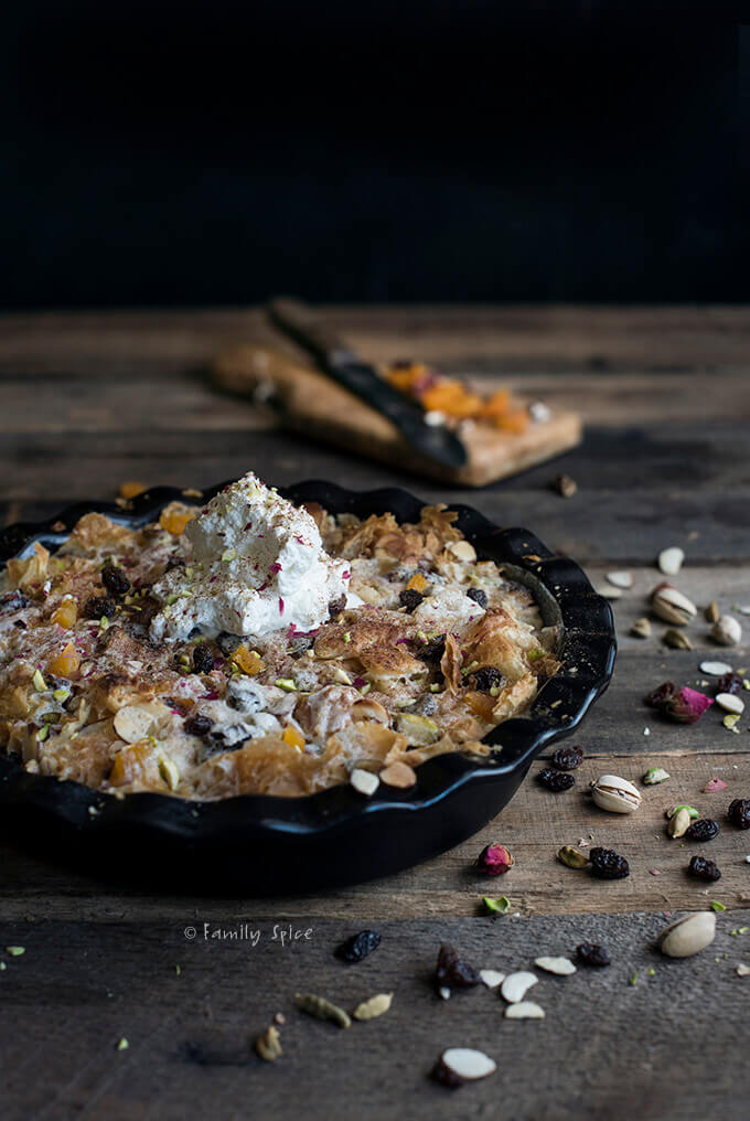 A small bowl of Egyptian Bread Pudding (Om Ali) with a cup of hot tea by FamilySpice.com