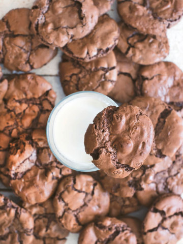 Top view of a white table covered in brownie cookies with a glass of milk in the center and a brownie cookie on the top of the glass