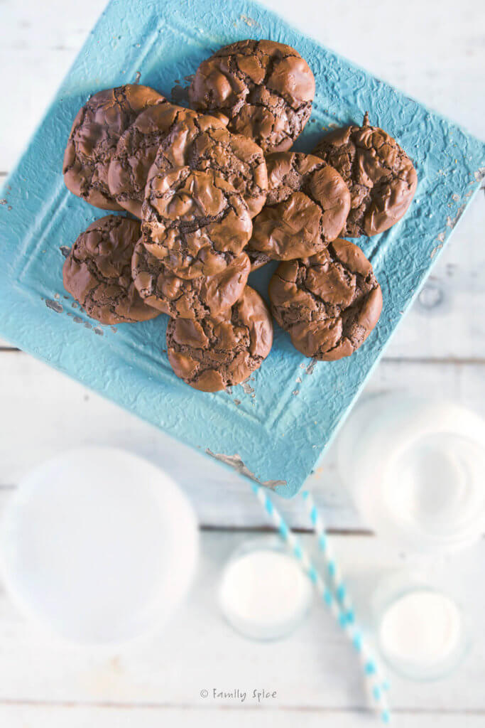 Top view of brownie cookies on a blue cake stand with white bowls and glasses of milk next to it