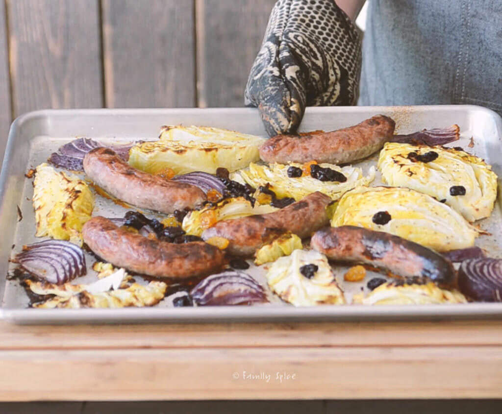 A baking sheet with freshly baked brats with onions and cabbage and raisins