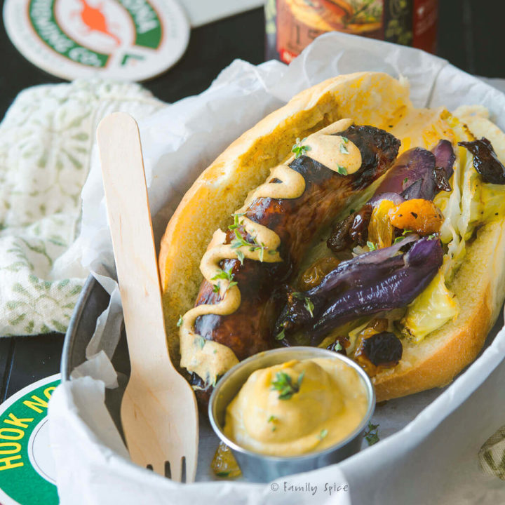 Oven baked bratwurst on a hoagie with mustard, roasted cabbage and red onions in a hoagie roll and in a metal food basket