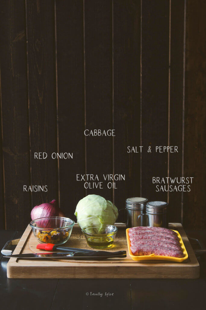 Ingredients labeled and needed to make brats in the oven with cabbage, onions and raisins