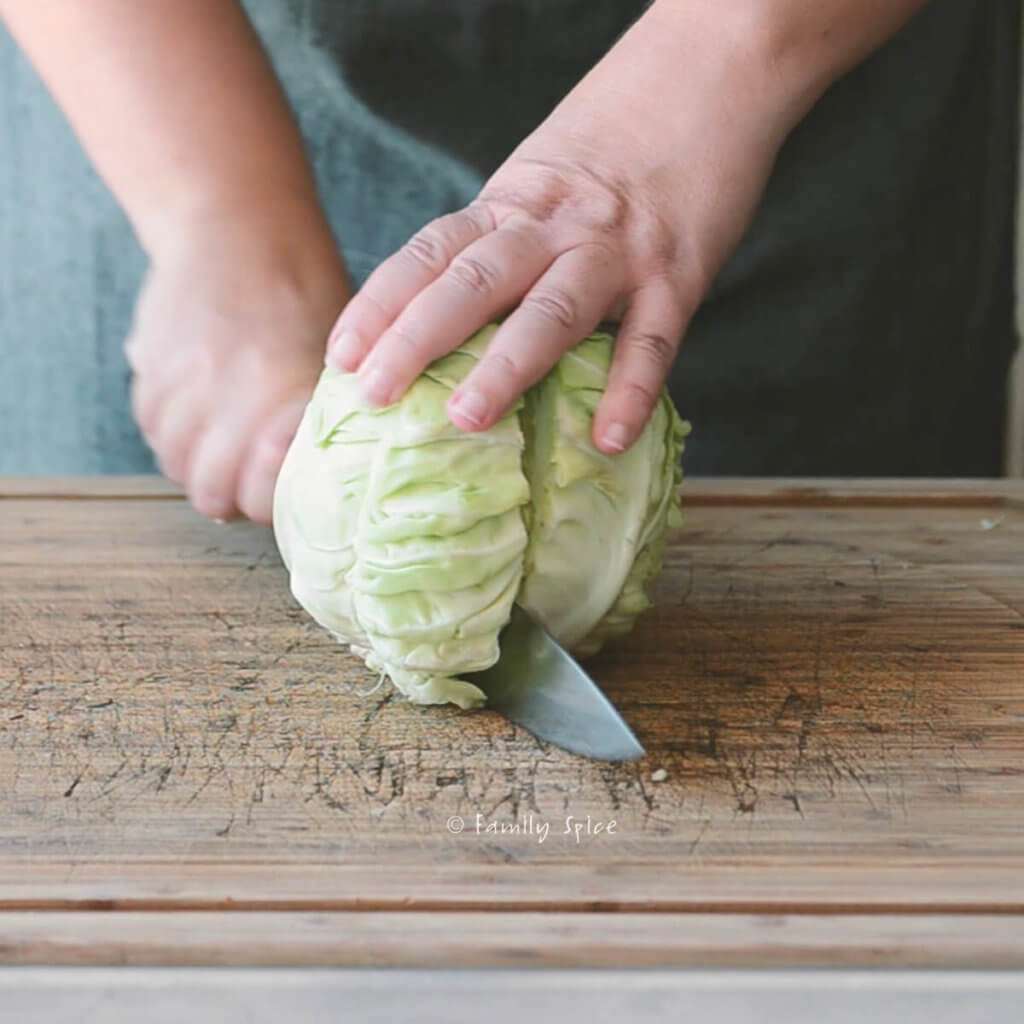 Cutting a green cabbage in half on a wooden cutting board