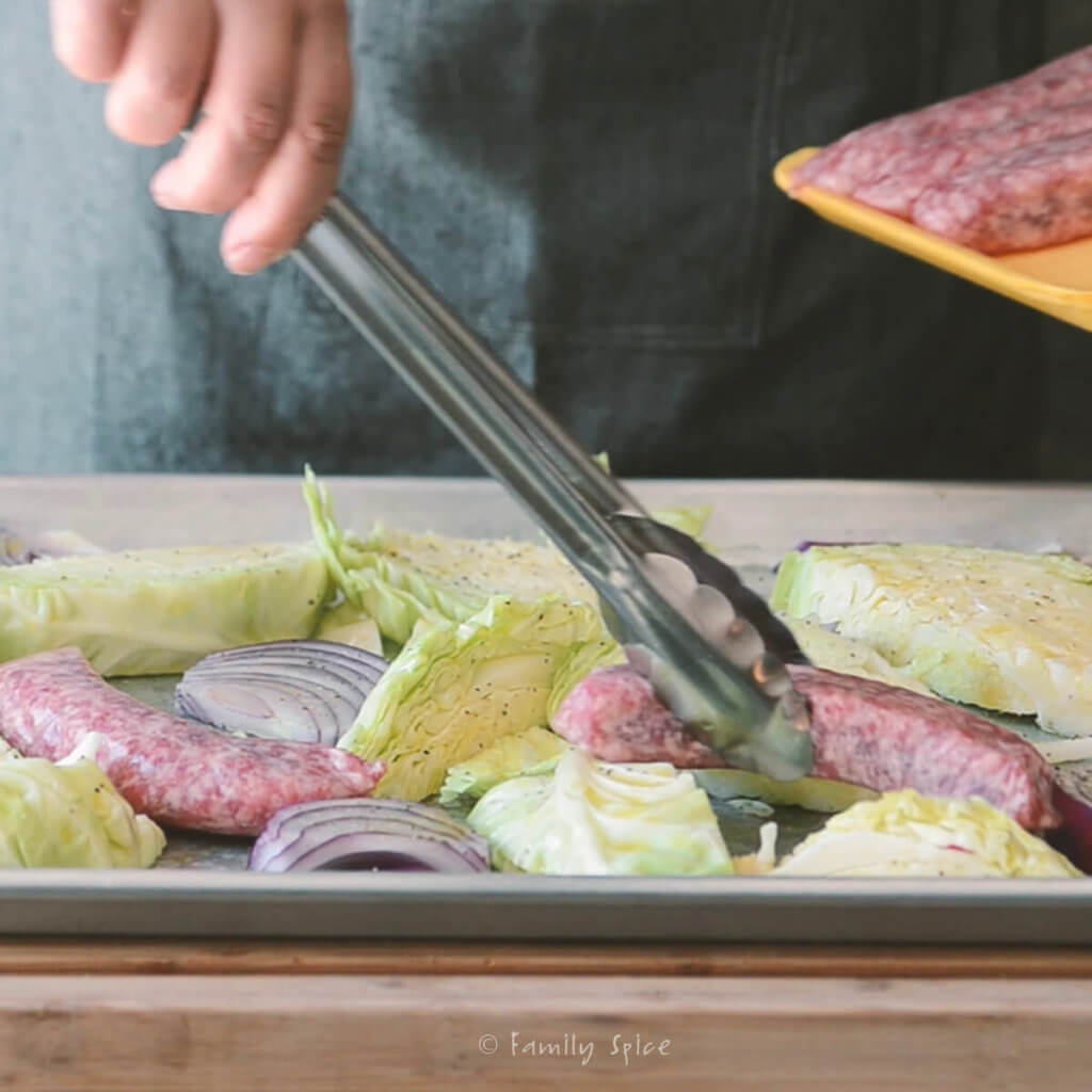Using tongs to place brats on a baking sheet with wedges of cabbage and red onions