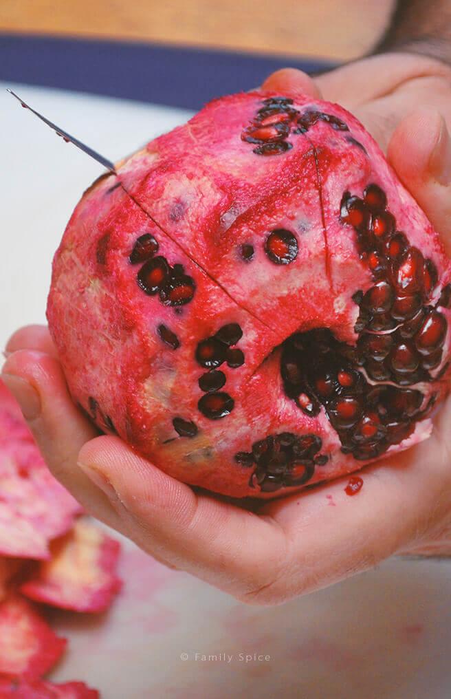 Scoring pomegranate in the segments by FamilySpice.com