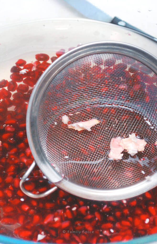 Pomegranate pith getting strained out of bowl of water filled by Pomegranate arils by FamilySpice.com