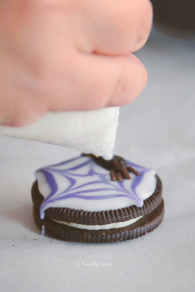 Icing eyes onto raisin spider cookie