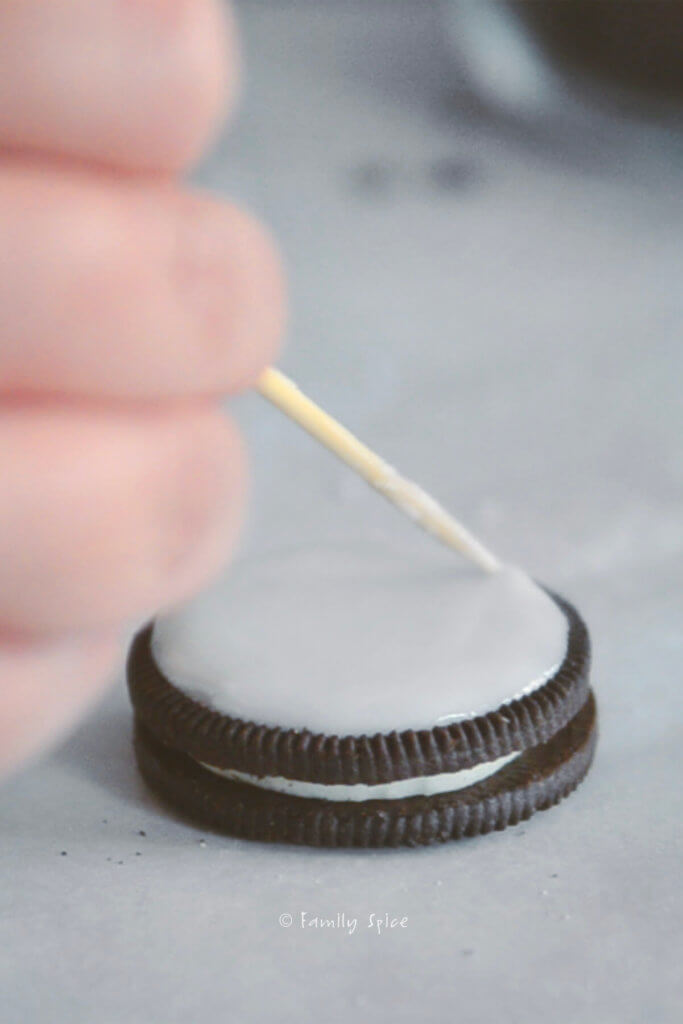 Using a toothpick to spread icing onto a chocolate cookie