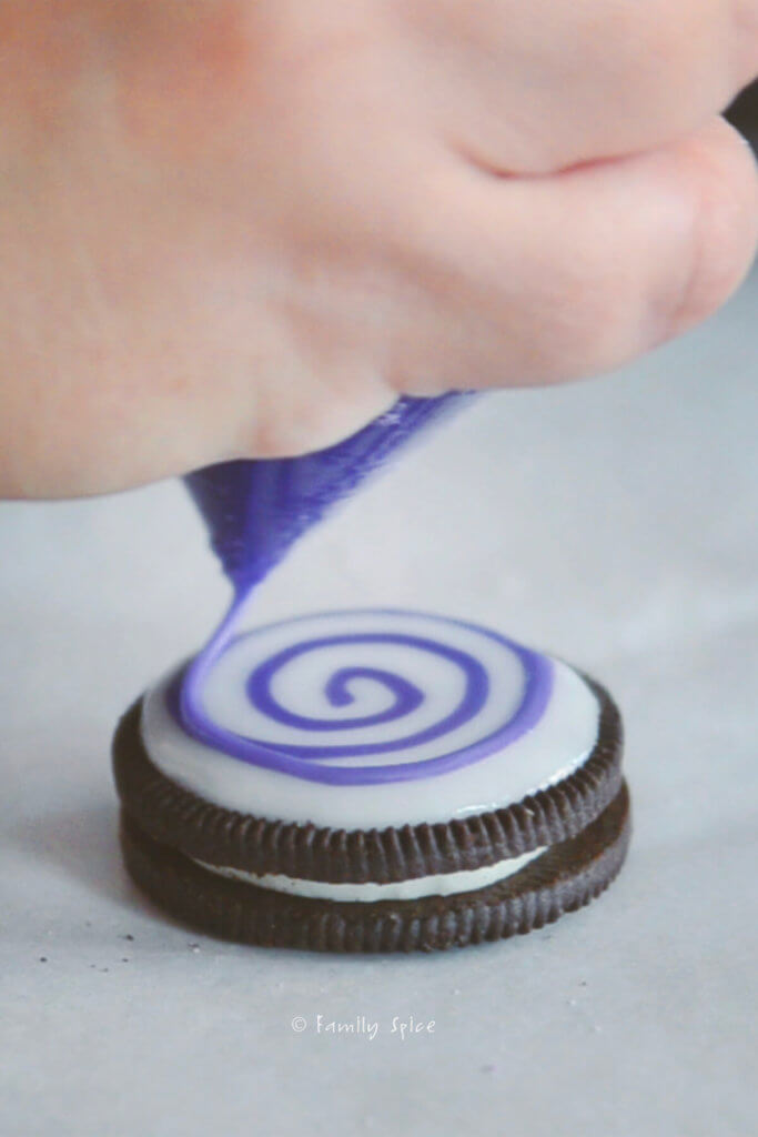 piping purple spirals that will be spider webs on cookie