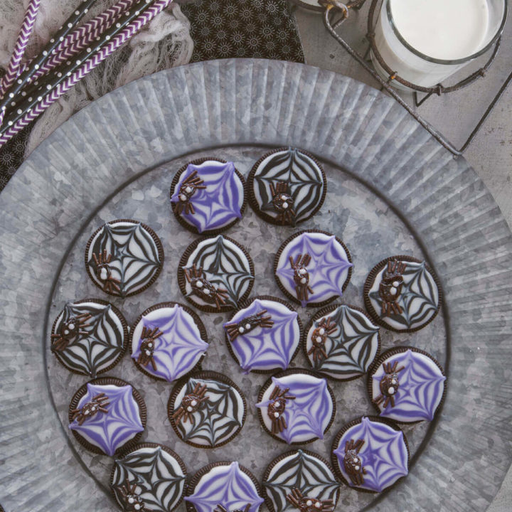 Overhead view of raisin spider cookies on a rustic metal tray with glasses of milk and black and purple straws