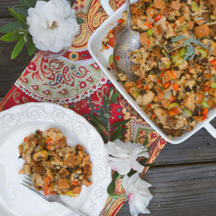 Overhead view of serving dish with cajun stuffing and a plate with stuffing on it
