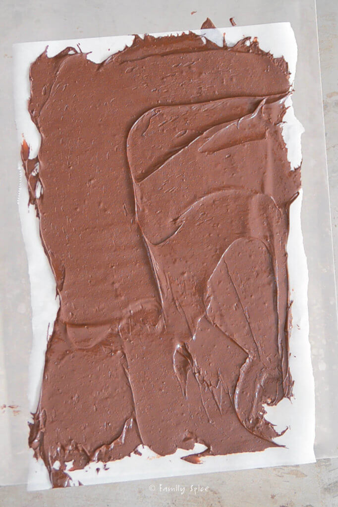 Top view of a sheet of parchment paper spread with melted chocolate