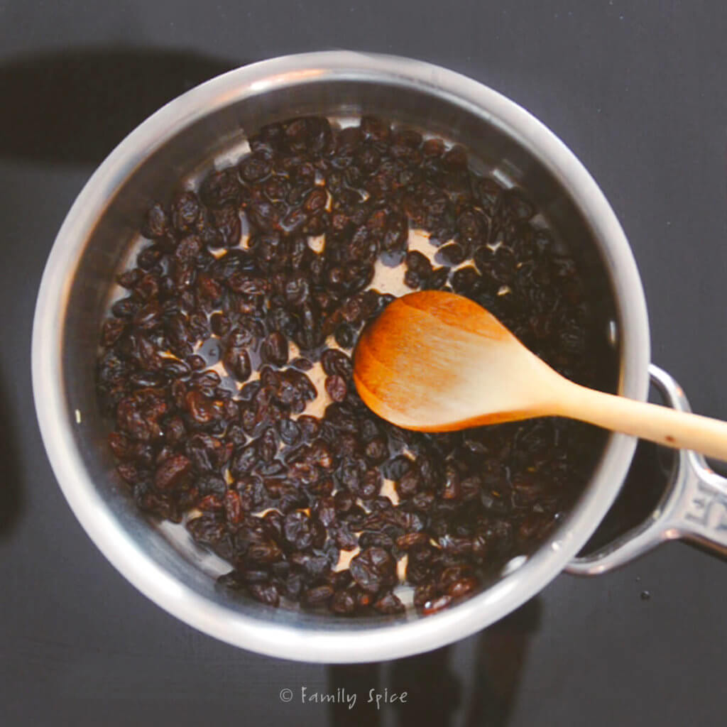 Soaking raisins in sweet liqueur syrup in a small pot