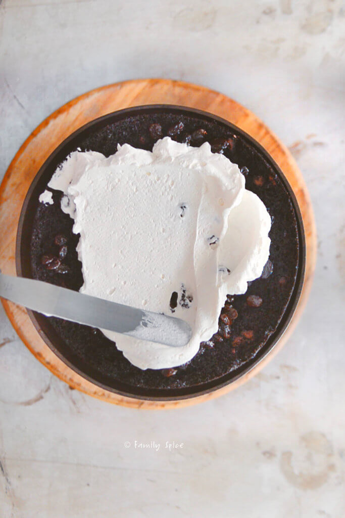 Top view of a chocolate cake with raisins getting frosted with whipped cream