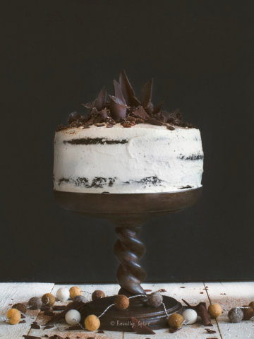A whipped cream frosted raisin black forest cake with chocolate shards on top on a dark brown cake pedestal