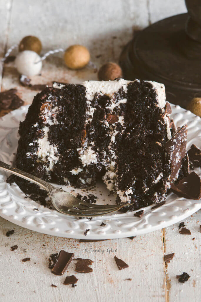 A big slice of raisin black forest cake on a white plate