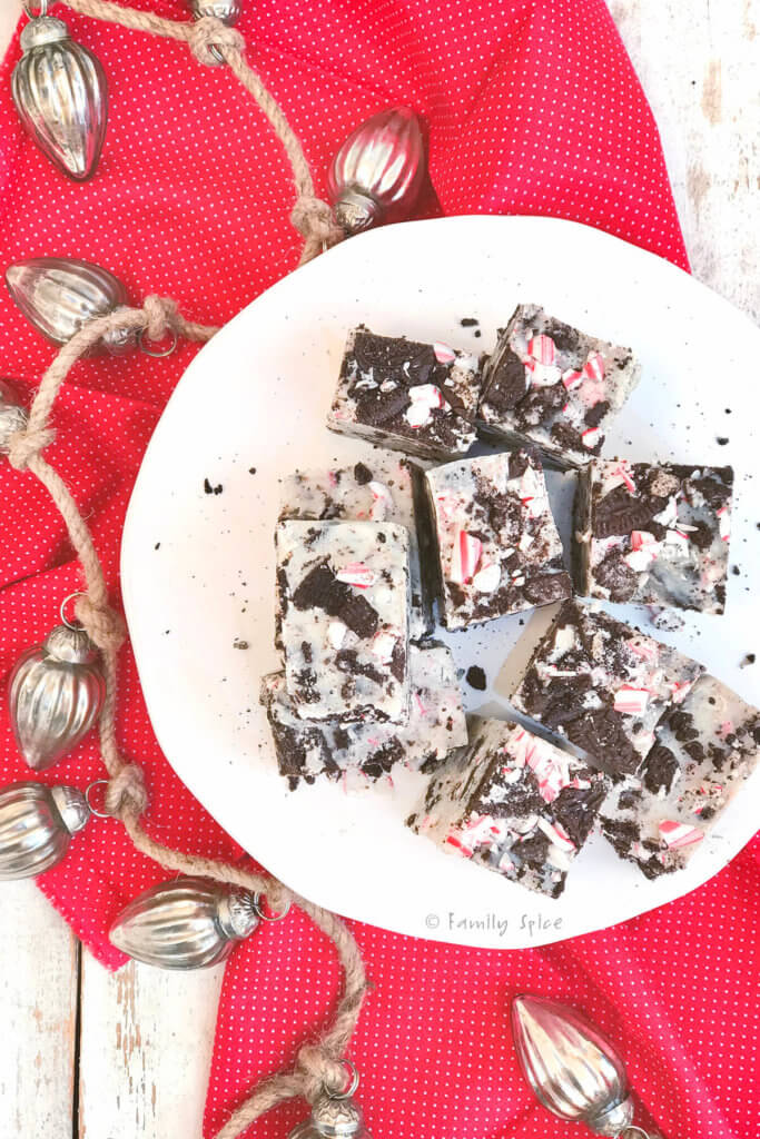 Overhead view of several cubes of peppermint oreo fudge on a white cake stand with holiday garland around it