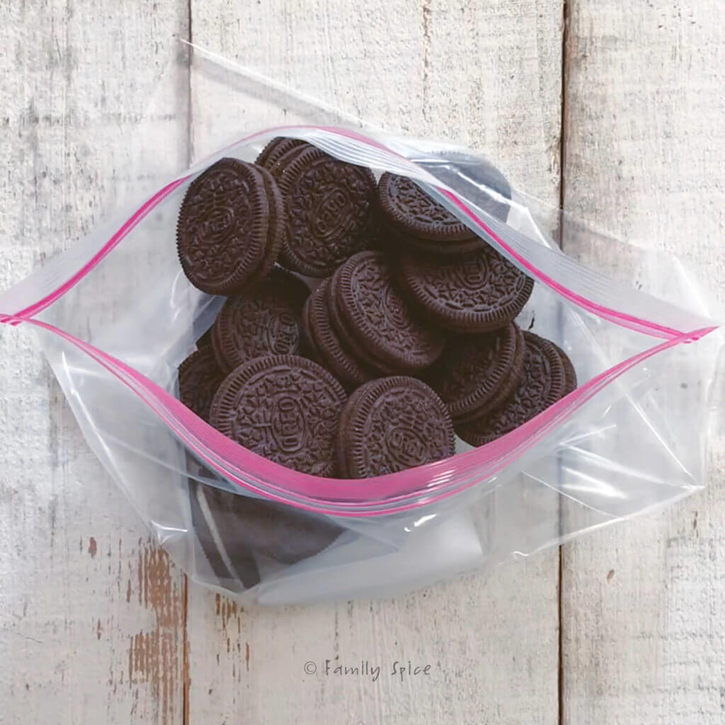 Oreos in a resealable bag on a white wood background