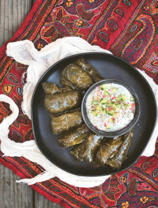 Overhead shot of a plate full of Persian dolma (or dolmeh/dolmades), stuffed grape leaves with a bowl of yogurt dip