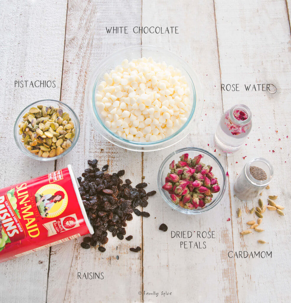 Ingredients labeled and needed to make white chocolate bark topped with pistachios, raisins and roses