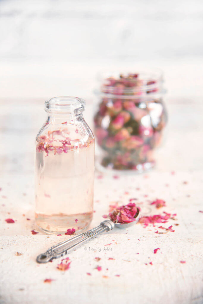 A small bottle with rose water and a jar of culinary dried rose petals