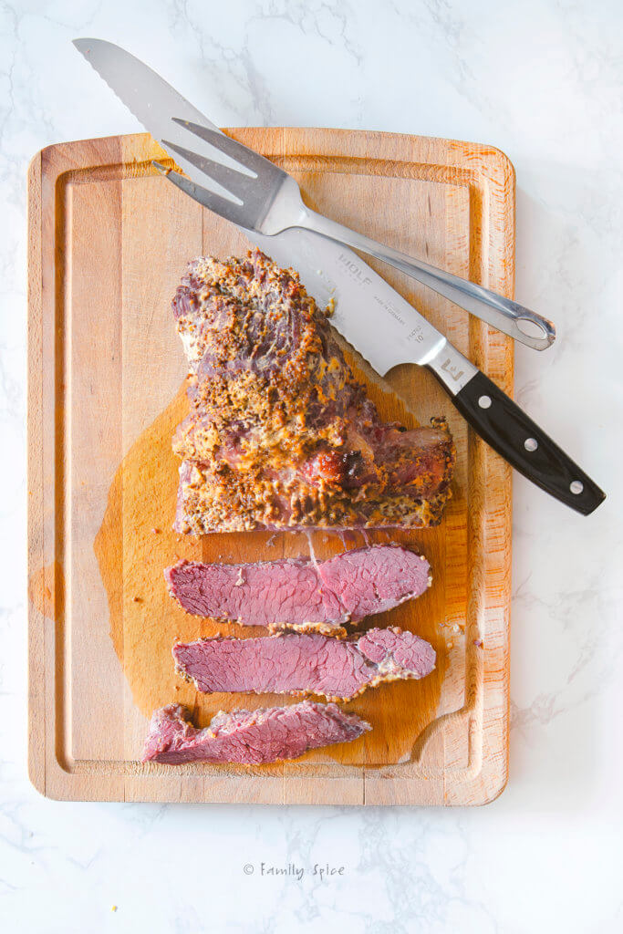 A baked corned beef brisket on a cutting board with a knife and fork and slices of meat