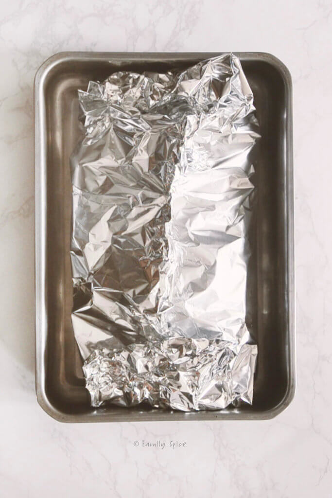 A corned beef roast wrapped in foil in a baking pan
