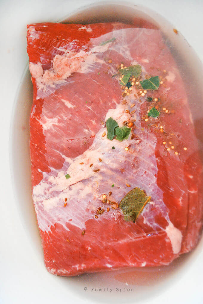 Raw corned beef roast in a crock pot with water by FamilySpice.com