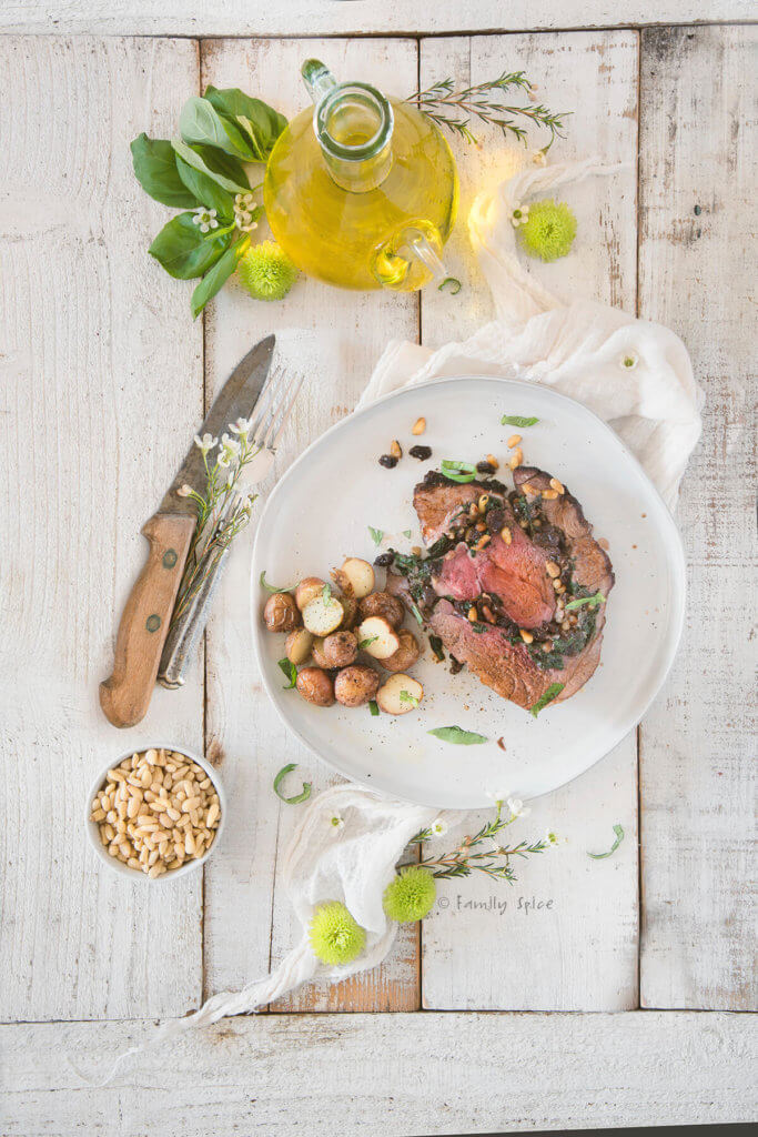 A white plate with a slice of boneless leg of lamb stuffed with spinach, raisins and pine nuts, served with potatoes with flowers around it