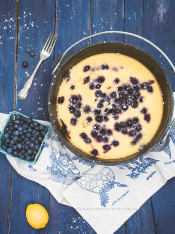Dutch Oven Lemon Blueberry Clafoutis with a carton of fresh blueberries